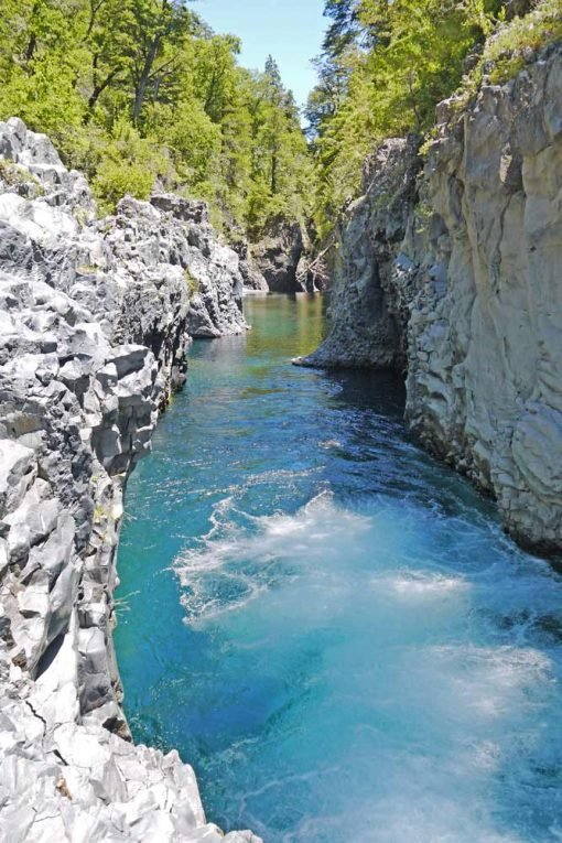 Ice blue water in the canyon surrounded by the forest, Siete Tazas, Chile