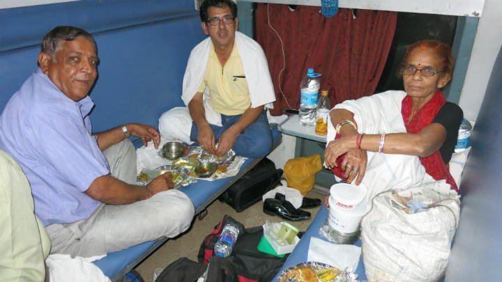 A family sharing their food with me in AC third class cart. India train travel.