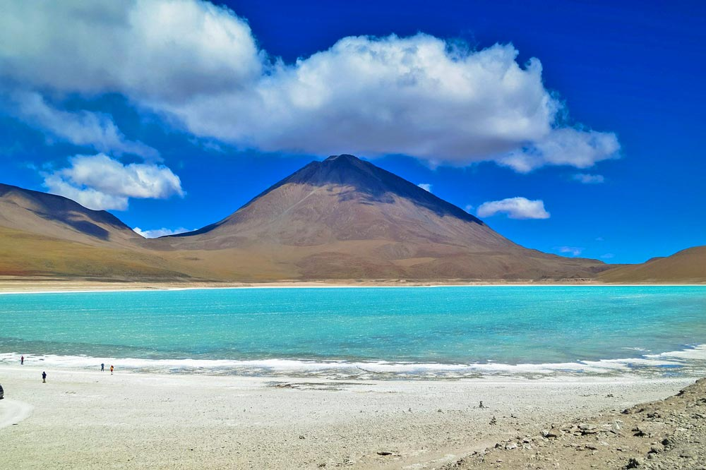 Turquoise water of the Laguna Verde and volcanoes around.