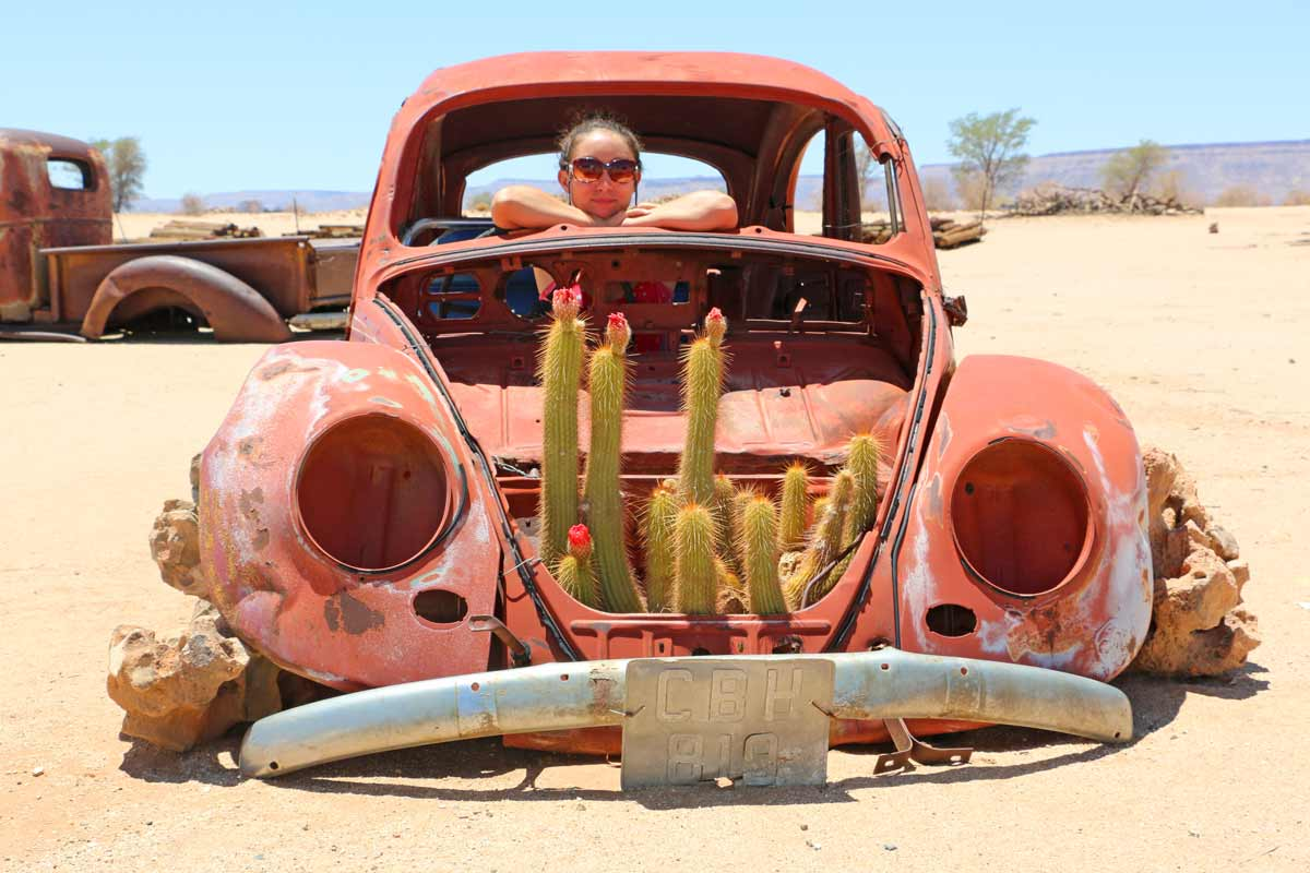 Alya sitting in an old rusted car with planted cacti in Namibia