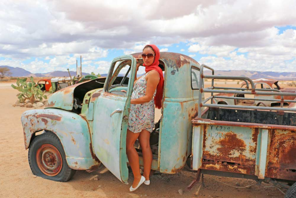 Alya in a rusted car at Solitaire stop in Namibia