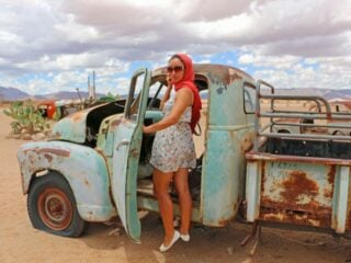 Alya in an old abandoned car at one of the stops on the road trip