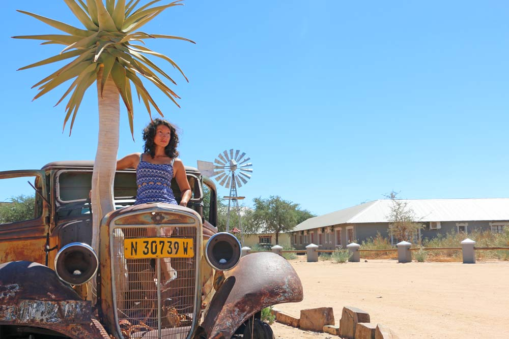 Alya in an old rusted car at Canyon Roadhouse on Namibia road trip