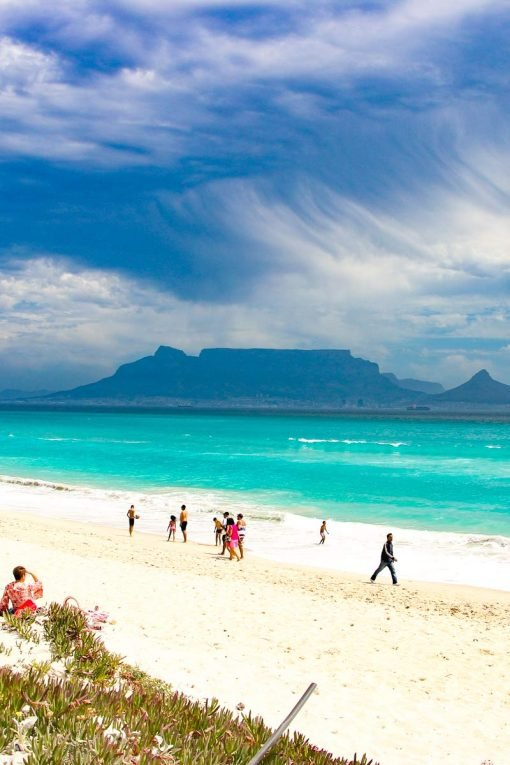 Stormy sky, turquoise blue water, white sand beach and Table Mountain on the background