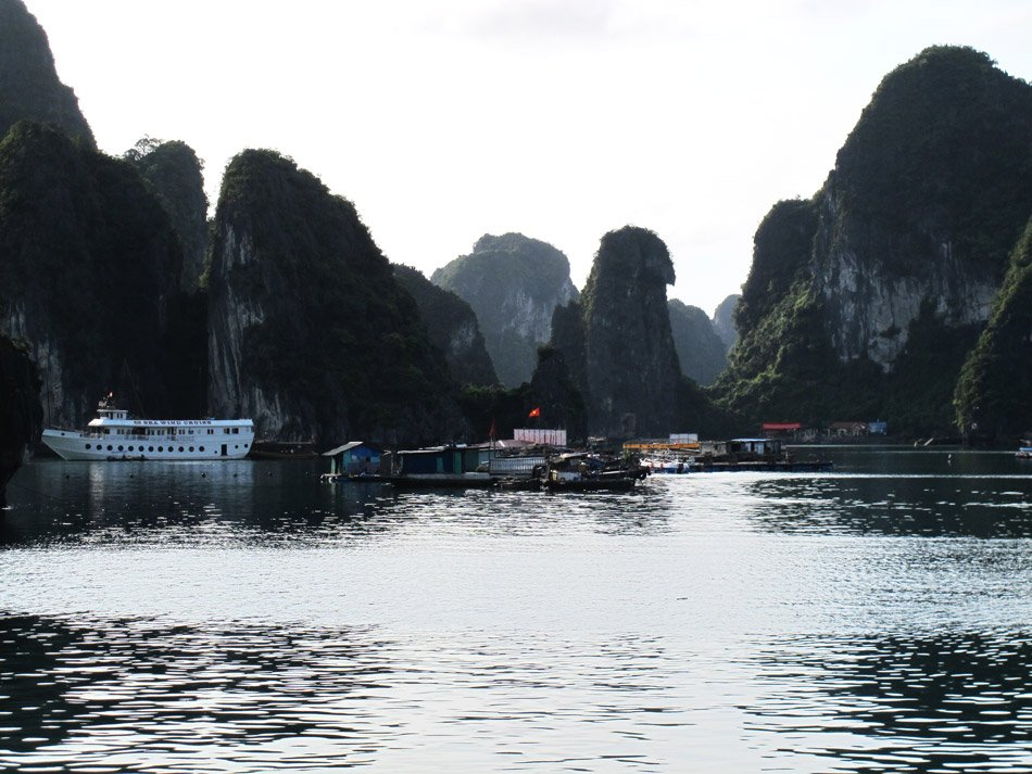Cruising between towering limestone islands on the emerald water of Halong Bay.
