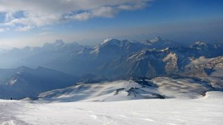 A view of a mountain range with snowy peaks from Elbrus