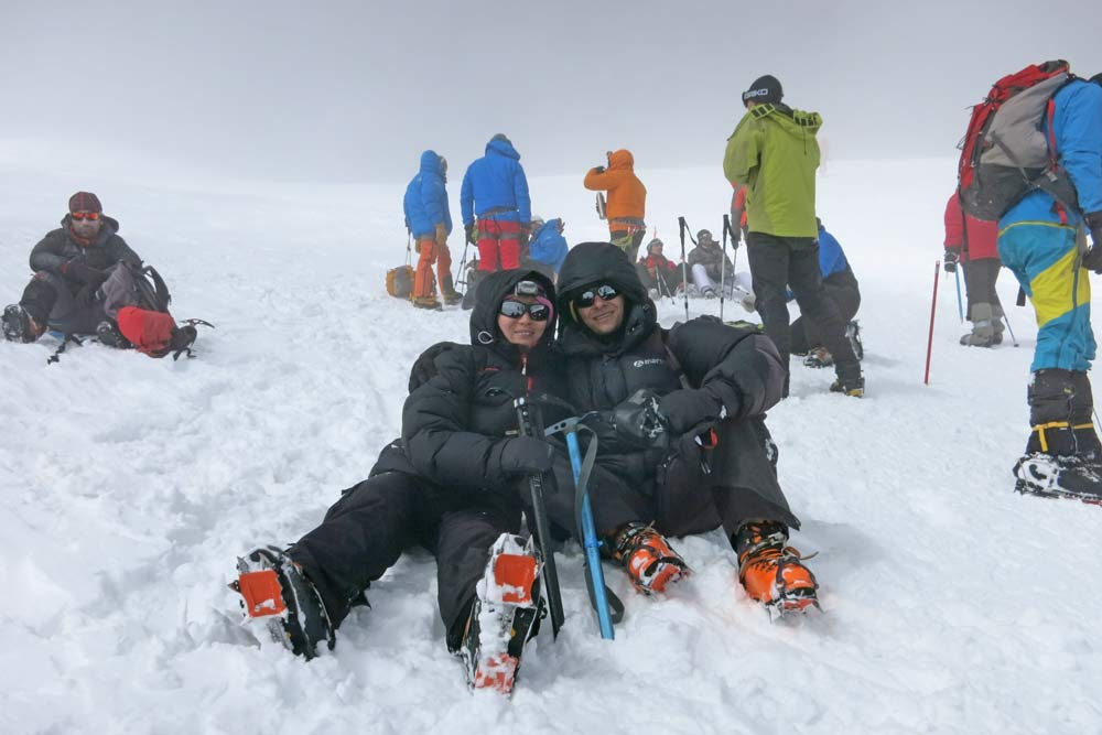 Campbell and Alya sitting on the snow and resting during the final ascent to Mount Elbus