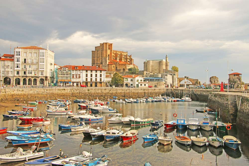 Many colorful boats and a castle on the background in the port of Castro Urdiales, Camino del Norte, Spain