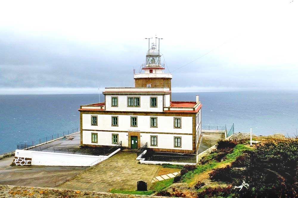 The Cape Finisterre lighthouse on the cliff surrounded by the sea