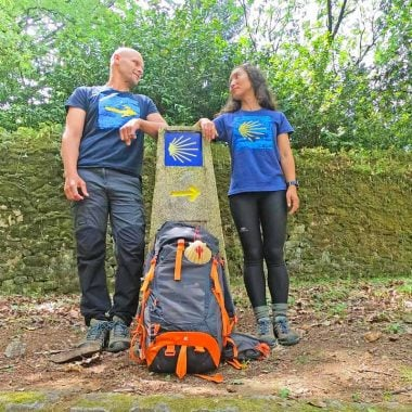Campbell & Alya wearing Camino T-shirts at a distance pole marking the Camino de Santiago in Galicia