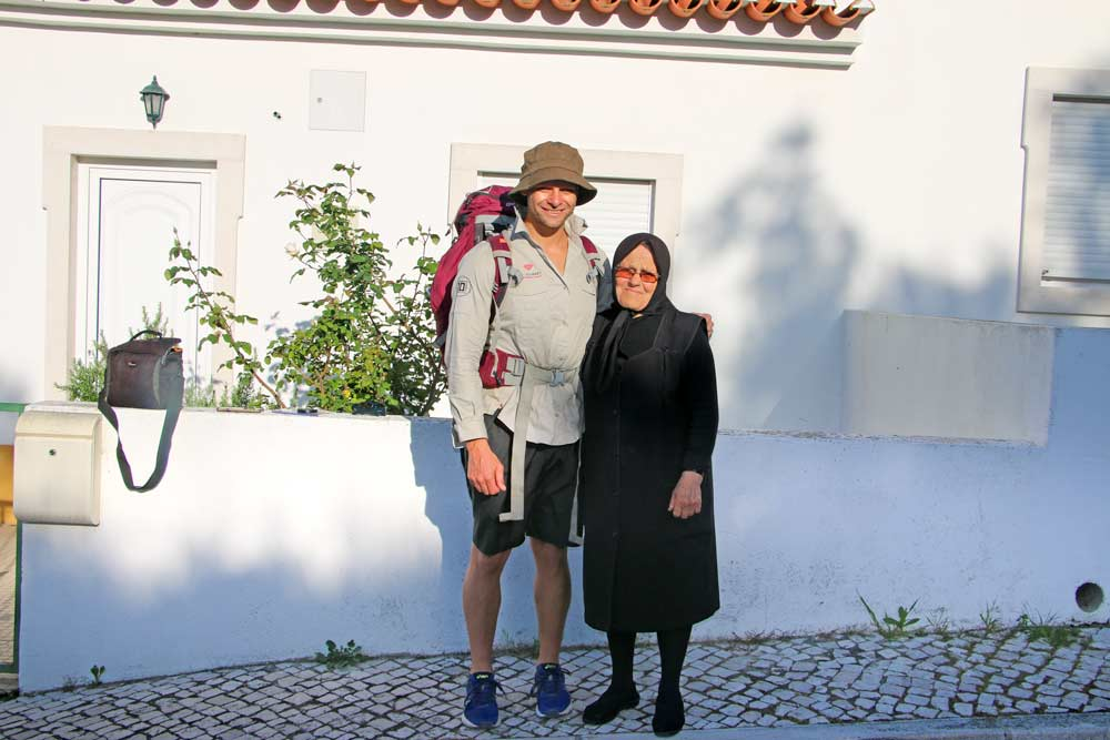 Campbell & doña Rosa standing next to a small white house in rural Portugal