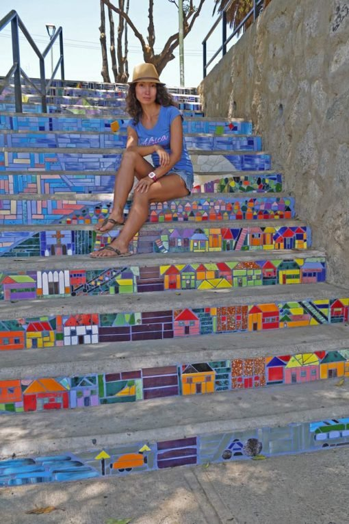 Alya sitting on the mosaic stairs in Valparaiso, Chile