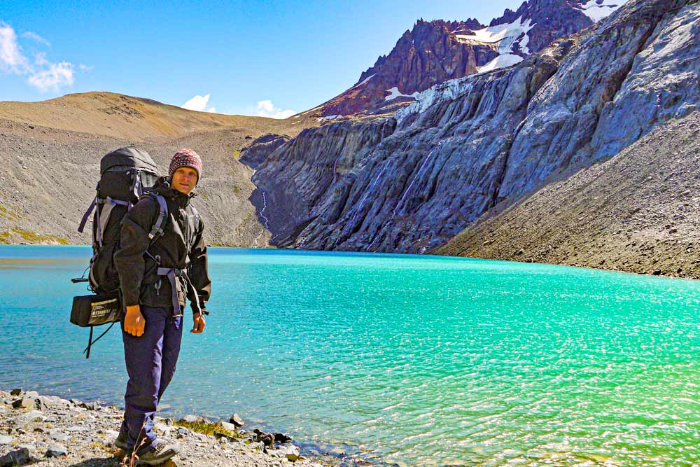Campbell with a backpack at the small green lake on the Cerro Castillo hike in Patagonia