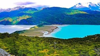 Two colorful lakes between lush green mountains in Patagonia