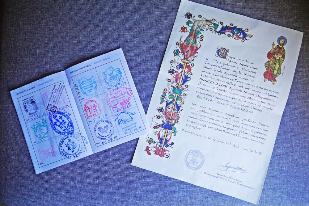 Alya's pilgrim passport with stamps from different albergues and the Compostela
