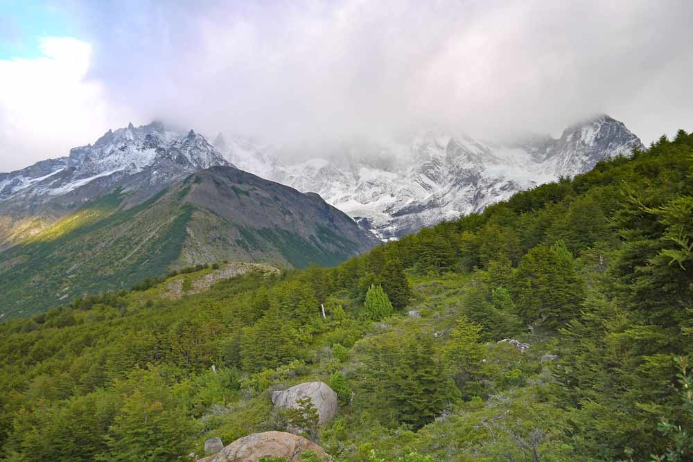 Mountainous scenery with snowy peaks and clouds on a hike in Torres del Paine