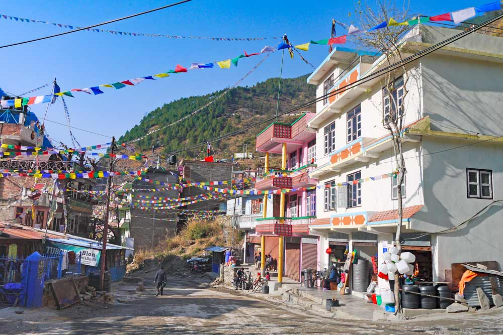 The main street of Syabrubesi decorated with Tibetan prayer flags