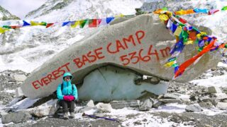 Alya sitting at the rock marking Everest Base Camp