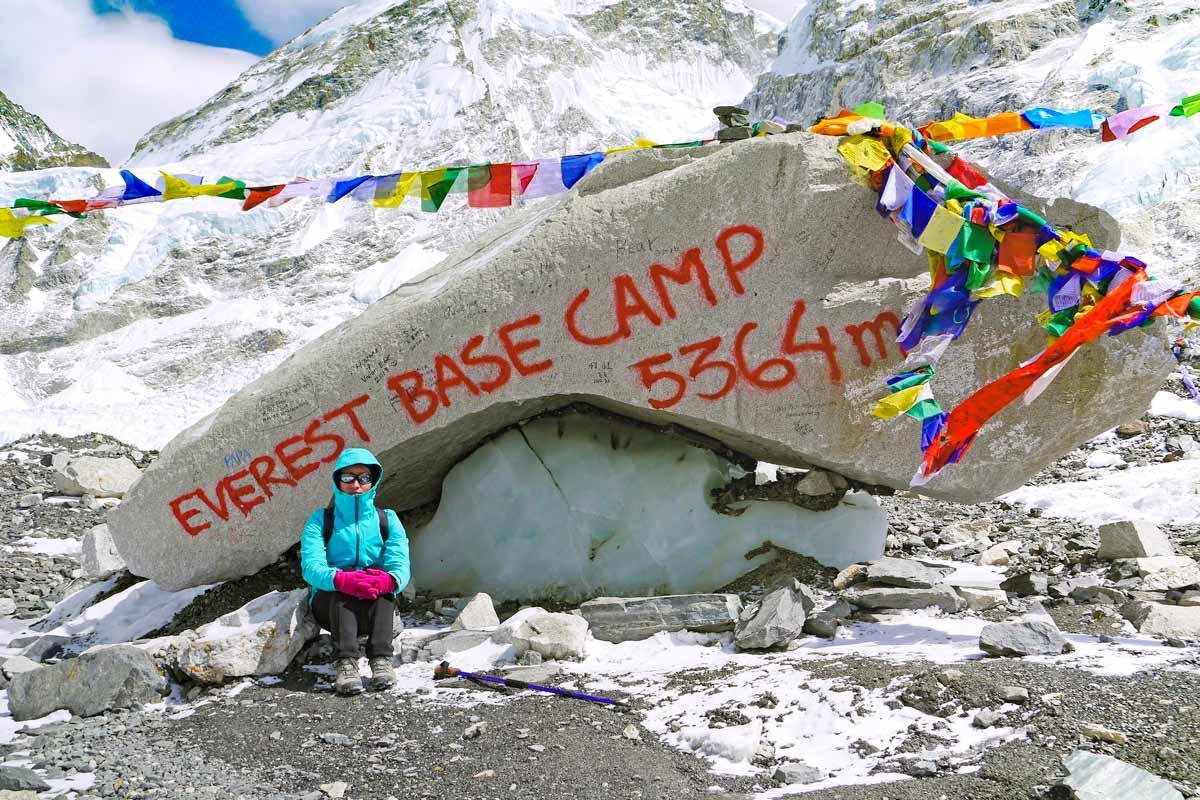 Alya sitting at the rock marking Everest Base Camp