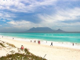 White sandy beach and the turquoise sea with Table Mountain on the background