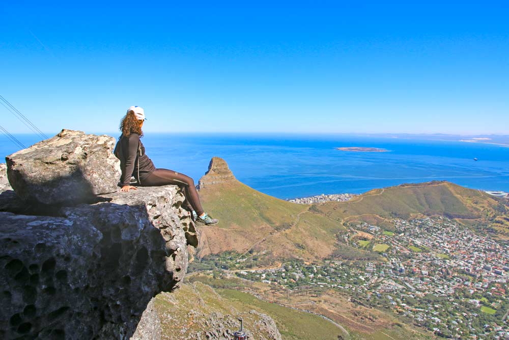 Alya on the edge of a rocky cliff looking at Lion's Head mountain