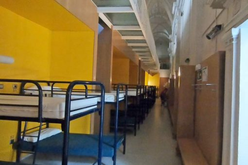 Many bunk beds in the line along the wall in a municipal albergue on the Camino