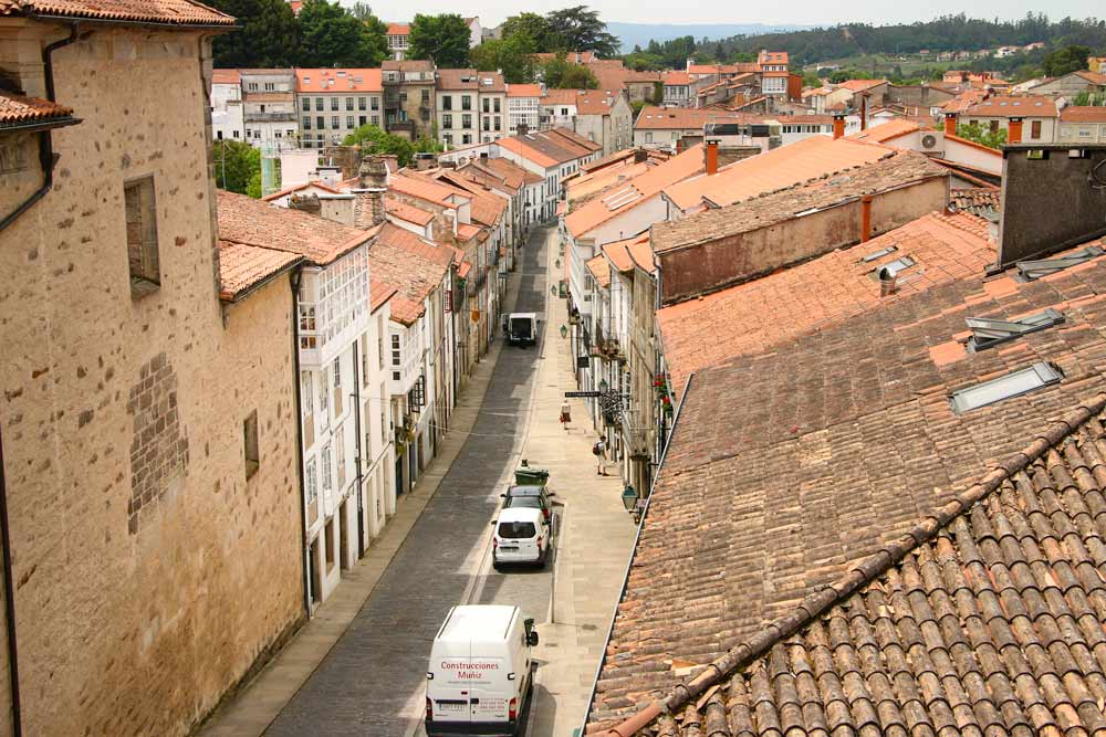 A narrow street with red-roof houses in the center of Santiago de Compostela, Spain