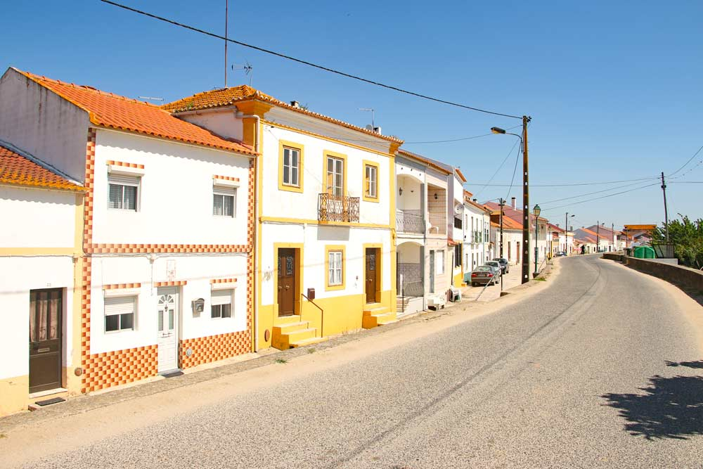 White houses with colorful windows lined along a quiet street of a small Portuguese town