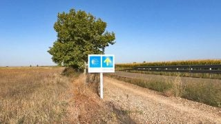 A blue sign with a yellow shell and arrow next to the dust road on the Camino route