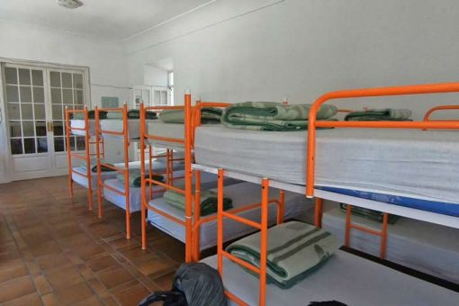 A dormitory with many metal bunk beds next to each other