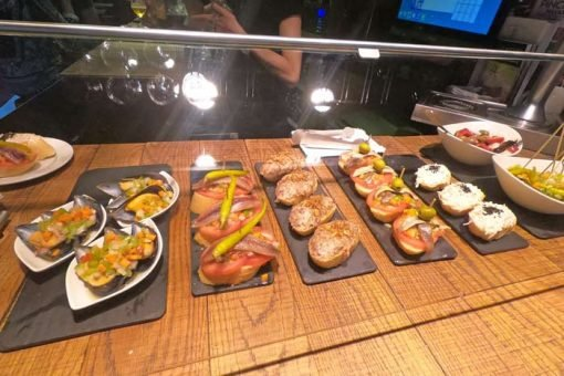 Different seafood and cold meat pintxos (small sandwiches) displayed at a bar