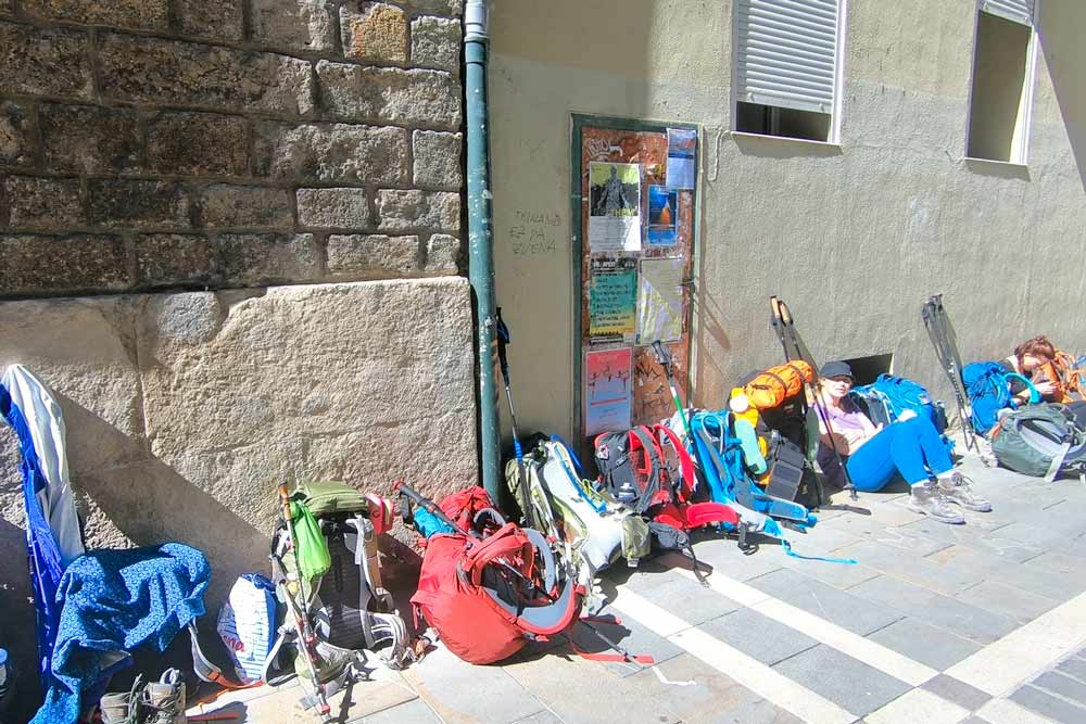 A backpack queue at the entrance of an albergue on the Camino