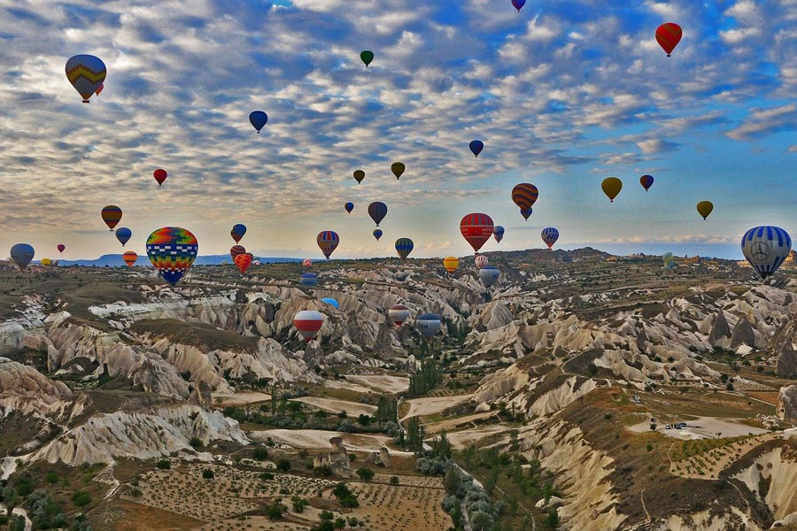 Hot air balloons floating over the spectacular landscapes of Cappadocia at sunrise.