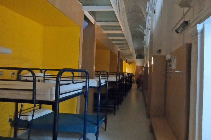 A dormitory room with many bunk beds in a municipal albergue on the Camino