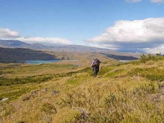 Campbell on a hiking trail in Patagonia carrying all his camping gear