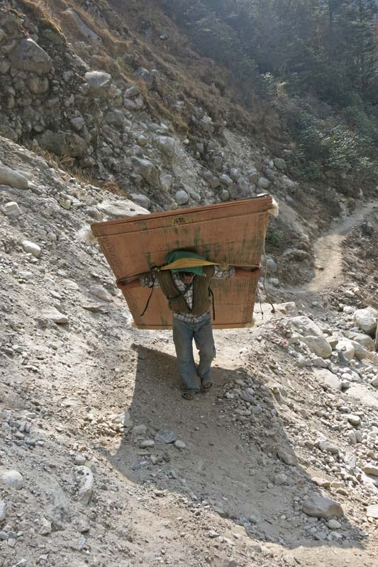 Porter carrying building material to EBC