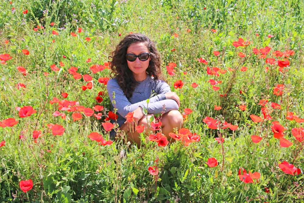 Alya in the field of poppies on the Camino in May